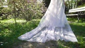 Отслеживать съемку невесты идя в солнечный зацветая сад в замедленном движении акции видеоматериалы