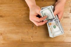 Отсчет человека новые доллары США на деревянном столе стоковые изображения rf