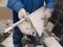 Отход конструкции и старая плитка в руке стоковые фото