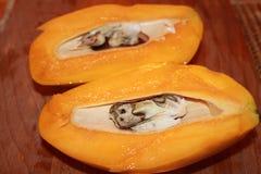 Отрезанное манго с косточкой на деревянной разделочной доске кухни стоковые фотографии rf