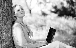Офис окружающей среды Преимущества outdoors работы Женщина с ноутбука работы деревом outdoors постным Минута для ослабляет девушк стоковые изображения rf