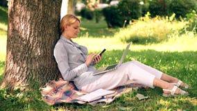 Офис окружающей среды Преимущества outdoors работы Женщина с работой ноутбука outdoors Технология образования и акции видеоматериалы