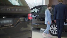 Официальные одетые счастливые пары идя между строками новых автомобилей в мотор-шоу для выбора одного Багажник автомобиля на пере акции видеоматериалы