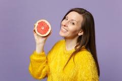 Очаровывая молодая женщина в свитере меха держа в половине руки свежего зрелого грейпфрута изолированного на фиолетовой пастельно стоковое фото rf