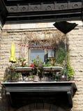Очаровывая небольшой балкон с цветками и заводами и побитым погодой зонтиком стоковая фотография