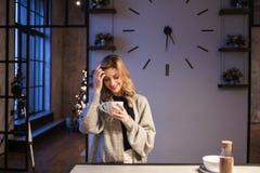 Очаровывая девушка в кухне на утре Говорить по телефону и иметь молодую женщину завтрака a с кружкой в ее руках стоковые фотографии rf
