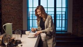 Очаровывая девушка в кухне на утре Говорить по телефону и иметь молодую женщину завтрака a с кружкой в ее руках стоковая фотография