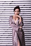 Очаровывать излучающе красивый женский posturing над striped предпосылкой стоковые изображения