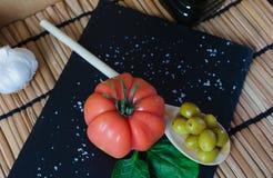 Очень вкусный томат raf на блюде шифера Соль, чеснок, оливковое масло и деревянная ложка с оливками среднеземноморское диетическо стоковые изображения rf