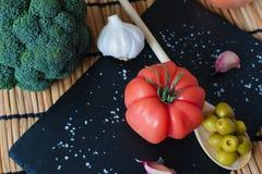 Очень вкусный томат raf на блюде шифера Соль, чеснок, оливковое масло и деревянная ложка с оливками среднеземноморское диетическо стоковое фото rf