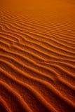 Оранжевая тонизированная предпосылка песка с волнистой картиной стоковые фото