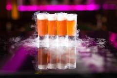 4 оранжевых съемки коктейля с дымом на отражательной таблице зеркала стоковая фотография