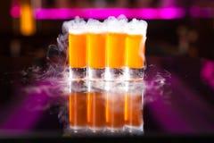 4 оранжевых съемки коктейля с дымом на отражательной таблице зеркала стоковое изображение