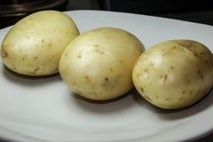 3 органических картошки на белой плите стоковые фото