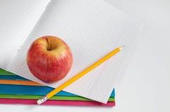 Ołówek i jabłko na szkolnym notatniku Obrazy Royalty Free