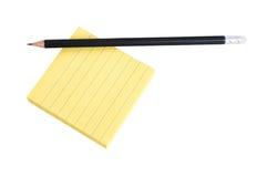 Ołówek na paczce notatki na biały tle Obrazy Royalty Free
