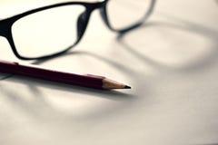 Ołówek na papierze z szkłami, biurowy biurko Zdjęcia Royalty Free