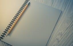 Ołówek na sprawdzać notatniku na drewnianym tle Obraz Stock