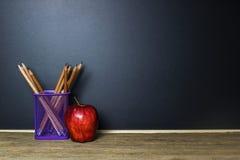 Ołówek w koszykowym i czerwonym jabłku na drewno stole z Blackboard Fotografia Royalty Free