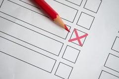 Ołówek z czerwonym krzyżem na białej księdze symbolizuje wybór zdjęcia stock