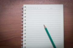 Ołówek z książką na drewnianym stole, rocznika stylu światło Zdjęcie Royalty Free