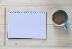 Ołówek z notatnikiem i filiżanką na drewnianym tle Obrazy Royalty Free