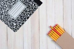 Ołówki i skład książka na drewno powierzchni Obrazy Royalty Free