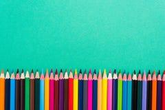 Ołówki obramiają kolorowego tło Zdjęcie Stock