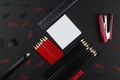 Ołówki w, zszywacz, klamerki, władca, nóż, czerwieni i czerni, i, biała księga na czarnym tle fotografia stock