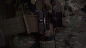 Żołnierz jest ubranym kamuflaż trzyma karabin szturmowego w zmierzchu Pionowo niecka zbiory
