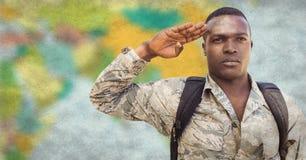Żołnierz salutuje przeciw rozmytej mapy i grunge narzucie z plecakiem Obraz Stock