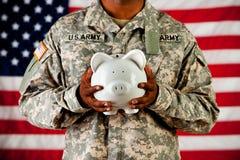 Żołnierz: Trzymać prosiątko banka obrazy stock