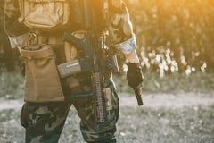 Żołnierz trzyma pistolet w występie zadania w kamuflażu i ochronnych rękawiczkach Obrazy Royalty Free