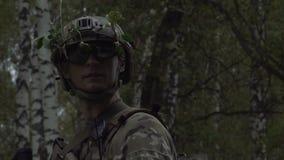 Żołnierz w hełmie i szkło stojaki na lasowym tle Militarny Kamuflaż zbiory