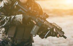 Żołnierz w występie zadania w kamuflażu i ochronnych rękawiczkach, trzyma pistolet Zdjęcie Royalty Free