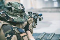 Żołnierz w występie zadania w kamuflażu, ochronne rękawiczki, hełm trzyma maszynowego pistoletu wp8lywy celuje dla strzału Obrazy Royalty Free