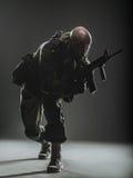 Żołnierza mężczyzna chwyta Maszynowy pistolet na ciemnym tle Zdjęcia Royalty Free
