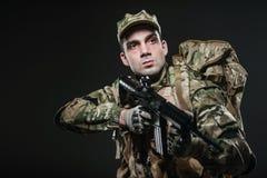Żołnierza mężczyzna chwyta Maszynowy pistolet na ciemnym tle Zdjęcie Royalty Free