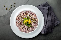 Ośmiornicy carpaccio Owoce morza ośmiornicy Surowi plasterki z oliwa z oliwek, cytryną i kaparami na bielu talerzu, Odgórny widok zdjęcia stock