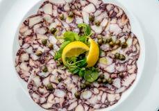 Ośmiornicy carpaccio Owoce morza ośmiornicy Surowi plasterki z oliwa z oliwek, cytryną i kaparami na bielu talerzu, Odgórny widok zdjęcie stock