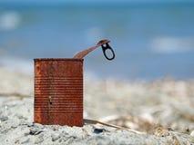 Ośniedziała blaszana puszka na plaży z błękitnym morzem obrazy royalty free
