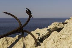 Ośniedziała kotwica przy skalistym wybrzeżem fotografia royalty free