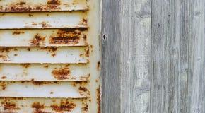 Ośniedziała stalowa żaluzja i drewniana ściana zdjęcia stock