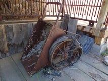Ośniedziały antykwarski przemysłowy przechylania wheelbarrow obrazy royalty free