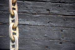 Ośniedziały kotwicowy łańcuch na tle stary drewniany dekoracyjny statek obraz stock