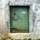 Ośniedziały metal zieleni drzwi na betonowej ścianie