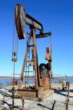 Ośniedziały pole naftowe Pumpjack kołysa konia nad wellhead Jasny b zdjęcie stock