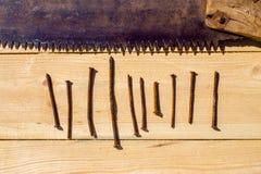 Ośniedziały zobaczył i dziesięć gwoździ na drewnianym stole Zdjęcia Royalty Free
