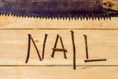 Ośniedziali gwoździe i ośniedziały saw na drewnianym stole Obraz Stock