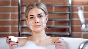 O ¡ de Ð perde-acima o retrato da mulher bonita com máscara de creme na cara durante a tomada do banho que olha a câmera video estoque